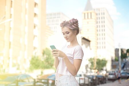 Portrait of a young stylish hipster woman walking down the street dressed in a trendy outfit, a pink hairstyle bun traveling around holding a mobile phone. Imagens
