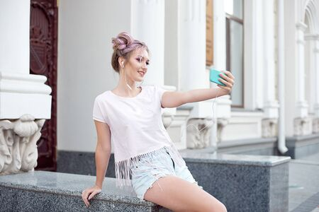 Young cute blonde and bright pink lips sitting on a bench, taking a selfie on her smartphone, in denim shorts, pink T-shirt Imagens