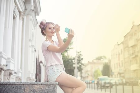 Young cute blonde and bright pink lips sitting on a bench, taking a selfie on her smartphone, in denim shorts, pink T-shirt. Imagens
