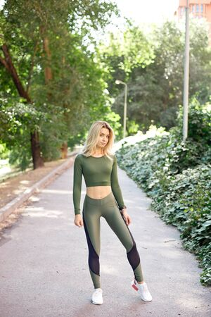 Young slim woman with a sporty body, long blond hair, dressed in a sports top and leggings, prepares for a morning jog in the park. Imagens