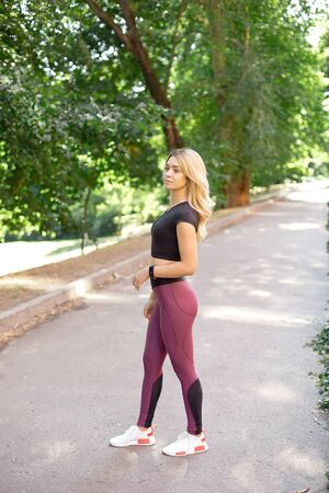 Fitness sport blonde girl in fashion sportswear doing yoga fitness exercise in the park, outdoor sports, urban style