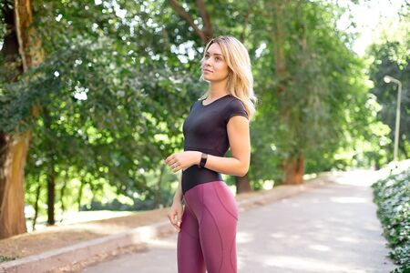 Young slim woman with a sporty body, long blond hair, dressed in a sports top and leggings, prepares for a morning jog in the park. Banque d'images