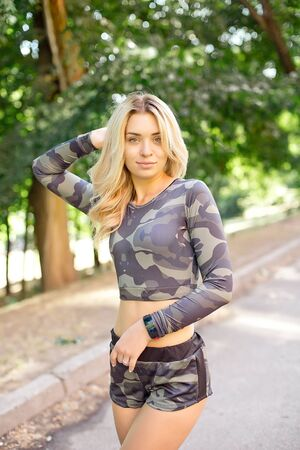 Close-up shot of fit young woman standing outdoors in the park. Muscular young woman in military sportswear looking forward Imagens