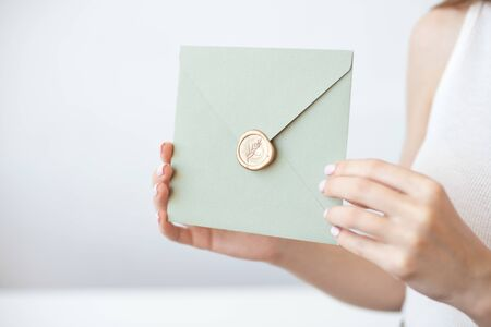 Close-up photo of female hands holding invitation envelope with a gold wax seal, a gift certificate, a postcard, wedding invitation card.