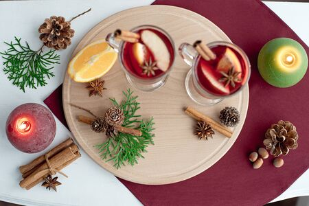 Winter hot tea with fruit, berries and spices in glass cup on white table. Top view, christmas decorations, copy space.
