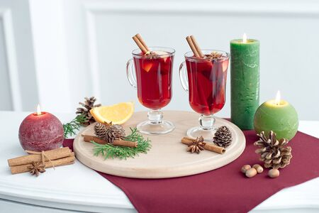 Two glasses of mulled wine with cinnamon sticks, a dry slice of oranges and cones, star anise on a white table Imagens