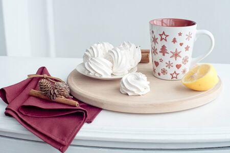 Cup of hot tea with fresh lemon health drink treat homemade marshmallows.