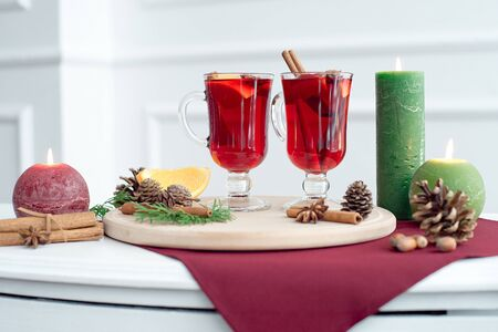 Christmas hot mulled wine with cinnamon, cardamom and anise on a white wooden background. Christmas table with hot drink, candles and wooden tray.