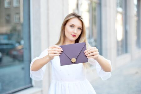Young woman with a gift in an envelope, a stylish envelope with a wax seal, held in her hands, looking up with a happy dreamy smile, thinking about her gift.