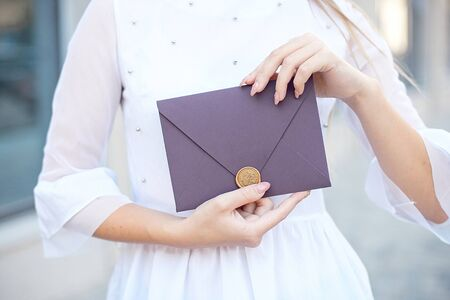 Young girl holds mail invitation cards in her hand. Envelopes with wax seal in hands close-up. Zdjęcie Seryjne
