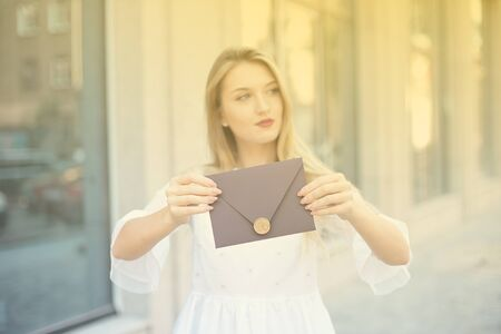 Young woman with a gift in an envelope, a stylish envelope with a wax seal, held in her hands, looking up with a happy dreamy smile, thinking about her gift. Zdjęcie Seryjne - 129009753