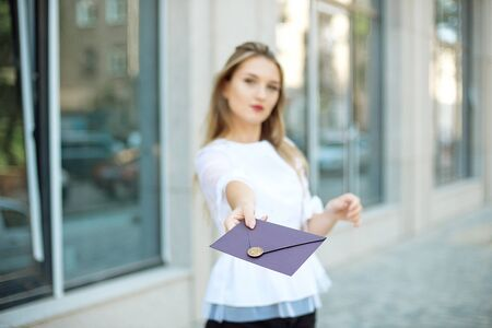 Young woman with a gift in an envelope, a stylish envelope with a wax seal, held in her hands, looking up with a happy dreamy smile, thinking about her gift. Zdjęcie Seryjne - 129009756