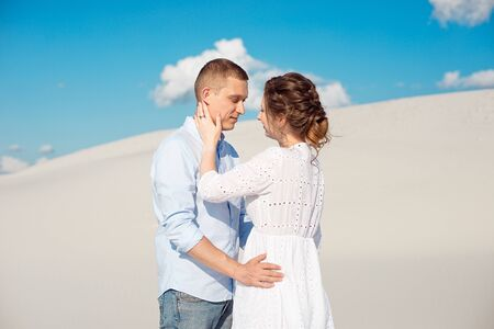 Young man and woman hugging on a background of white sand, dunes. Love story in the void. Reklamní fotografie