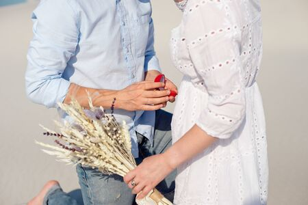 Handsome man makes marriage proposal to girl sand dunes Imagens