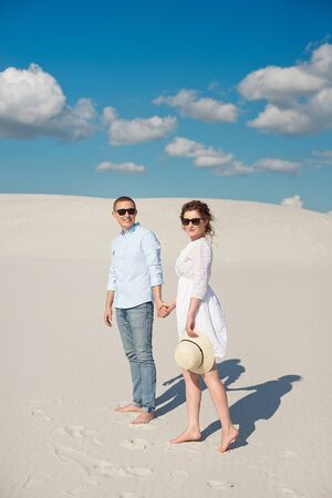 Young couple enjoying the sunset in the dunes. Romantic traveler walks in the desert. Adventure travel lifestyle concept