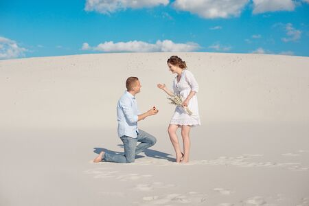 Handsome guy makes the girl a proposal for marriage, bending his knee, standing on the sand in the desert. Happy moments of family life.