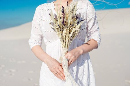 Close-up girl holds in her hands a wedding bouquet with dried flowers.