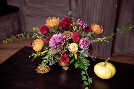 Happy Halloween pumpkin a copper vase with autumn flowers in the house. Romantic date getting ready for Halloween.