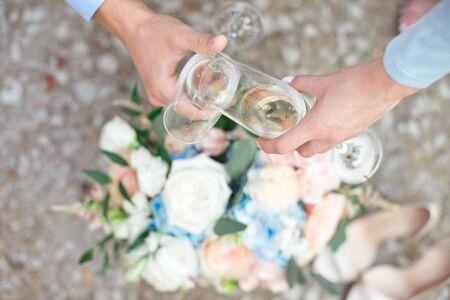 Bride and groom holding wedding champagne glasses Фото со стока
