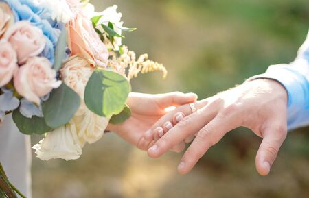 Bride wears groom a wedding ring Bride hand holds a beautiful wedding bouquet.