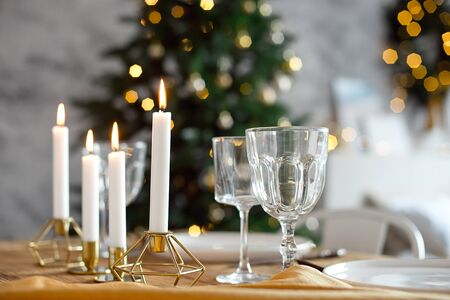 Table is served for a Christmas dinner in the living room, close-up view, table setting with a golden tablecloth, white plates, forks, knives, glasses for wine, candles in gold candlesticks, Christmas decorations