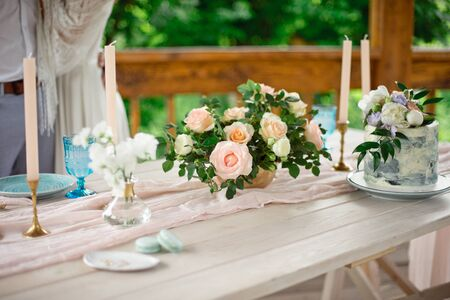 Wedding decoration table in the garden, floral arrangement, In the style vintage on outdoor. Wedding cake with flowers. Decorated table with flowers, served for two people Zdjęcie Seryjne