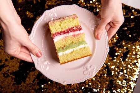 Golden brilliant tasty cake is cut into pieces. A slice of cake on a pink plate. Homemade baking for a children's party.
