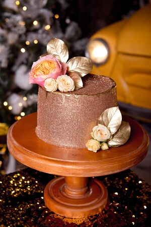 Chocolate cake with raspberry filling and pistachio cream, decorated with roses and golden jelly sparkles in the New Year's interior 版權商用圖片