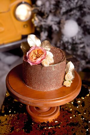 Chocolate cake with raspberry filling and pistachio cream, decorated with roses and golden jelly sparkles in the New Years interior.