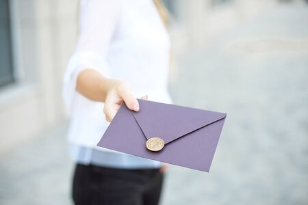 Young girl holds mail invitation cards in her hand. Envelopes with wax seal in hands close-up. 版權商用圖片