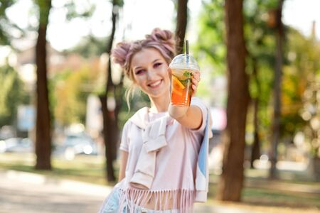 Beautiful urban teenager girl with bun and makeup dressed in a pink T-shirt and a sweatshirt holding a plastic cup with a cooling lemonade. 版權商用圖片