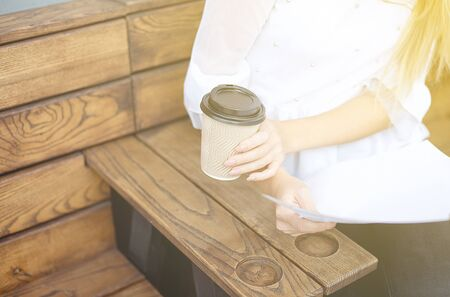 Young girl holds in her hand a paper cup of coffee or tea on a wooden table at a street food festival 版權商用圖片