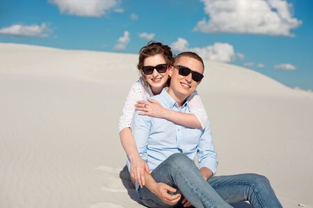 Photo of a gorgeous couple man and woman smiling and hugging on a sand hill.