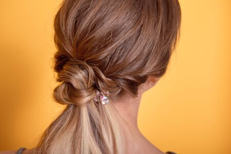 Rear view of female hairstyle middle bun with brown hair. 版權商用圖片