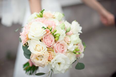 Close-up groom in a suit and the bride in a white dress are standing and holding a bouquet of peach roses, eustomas and flowers and greenery.