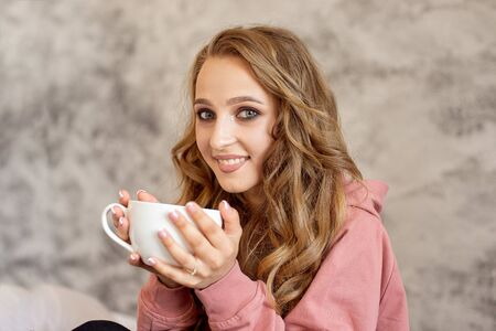 Teen girl sits on a bed in a winter warm sweater enjoying delicious homemade fruit tea.