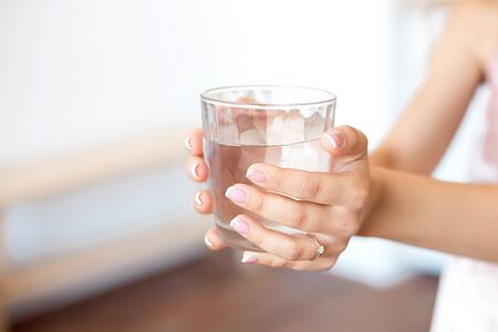 Female hands holding a transparent glass of water. Healthy lifestyle. 版權商用圖片