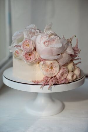 White wedding cake decorated with fresh roses, peonies and greenery