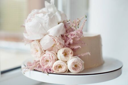 Decorated with fresh flowers, white naked cake, a stylish cake for weddings, birthdays and events.