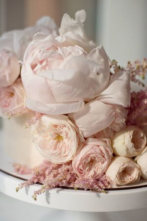 Sweet white cream cake round with pink roses flowers and white peony on top, valentine love, wedding concept.