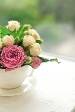 A bouquet of white roses in a cup on a white table opposite the window.