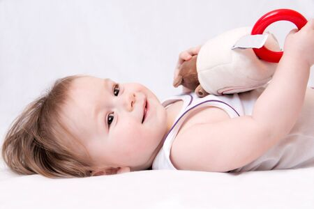 A small child lies on the floor with a toy on a white background. Photography of babies, childrens emotions. Use in childrens stores, websites, boards, etc.