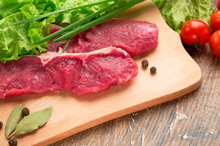 Fresh, crude stakes from meat veal on a wooden chopping board with setion,black pepper, lettuce leaves,fennel, bay leaf, green onions and cherry tomatoes