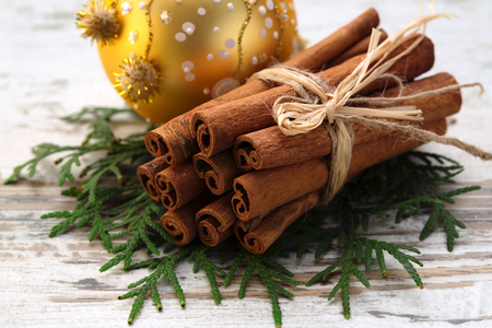 Traditional, Christmas decor, linking of sticks of spice of cinnamon on fir-tree branches with a round Christmas tree decoration of yellow color on a light wooden background close up Reklamní fotografie