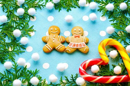 trabajo manual: Navidad, pan de jengibre jengibre tradicional en la forma del niño y la niña del trabajo hecho a mano, de cerca contra de las ramas de abeto y caramelo rayado