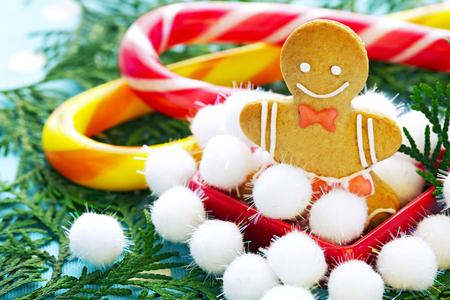 trabajo manual: Navidad, pan de jengibre jengibre tradicional en la forma del peque�o hombre del trabajo hecho a mano, de cerca contra de las ramas de abeto y caramelo rayado