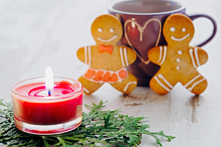 romantic heart: card for St. Valentines Day, gingerbreads little men against the heart represented on a cup, the burning red candle on fir-tree branches on a light wooden background close up