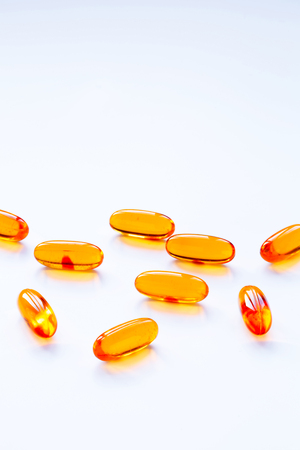 food additives: Biological additives to food, vitamins for a healthy lifestyle, capsules an omega 3 with cod-liver oil, transparent orange color an embankment on a light background close up