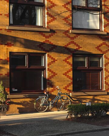 A bicycle is parked next to a residential building in a quiet street with a locking device. Thoughts on the ecological form of transport and a healthy lifestyle.