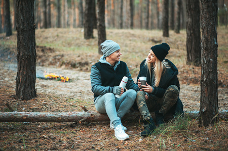 Romantic couple sitting near bonfire, autumn forest background. Young blonde woman and handsome man. Concept - family, togetherness, love, friendship, traveling.